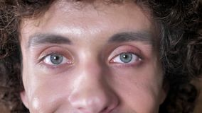 Het portret van de jonge mens met krullend haar en blauwe ogen die camera bekijken, sluit schot van mensen` s ogen stock video