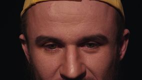 Het portret van de jonge vermoeide mens met baard in geel GLB glimlacht lichtjes stock video
