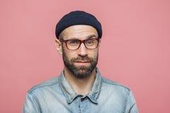 Het portret van de knappe gebaarde mens kijkt met tevreden verraste uitdrukking, draagt glazen en zwarte die hoed, over roze stud stock afbeeldingen