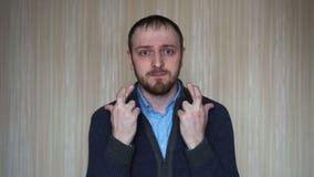 Het portret van de knappe jonge mens wordt gekruist zijn vingers en maakt een wens stock footage
