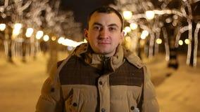 Het portret van de knappe mens bekijkt camera in openlucht tijdens koude de winterdag stock videobeelden