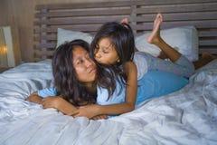 Het portret van de levensstijlslaapkamer van gelukkige Aziatische vrouw die thuis met weinig dochter in en vrolijk bed spelen die stock fotografie