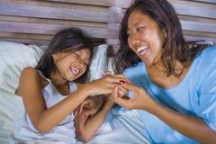 Het portret van de levensstijlslaapkamer van gelukkige Aziatische vrouw die thuis met weinig dochter in en vrolijk bed spelen die stock afbeeldingen