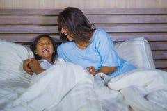 Het portret van de levensstijlslaapkamer van gelukkige Aziatische vrouw die thuis met weinig dochter in en vrolijk bed spelen die royalty-vrije stock fotografie