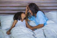 Het portret van de levensstijlslaapkamer van gelukkige Aziatische vrouw die thuis met weinig dochter in en vrolijk bed spelen die royalty-vrije stock afbeeldingen