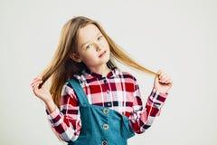 Het portret van de manier van een meisje het knappe jong geitje stellen in de studio Kinderen op haar worden opgeheven dat royalty-vrije stock afbeeldingen