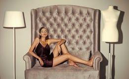 Het Portret van de Manier van de schoonheid Meisjesrust op grijze bank bij model en staande lamp Stock Foto's