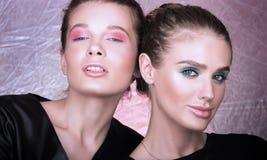 Het portret van de manierclose-up van twee mooie jonge vrouwen Heldere professionele make-up Stock Foto's