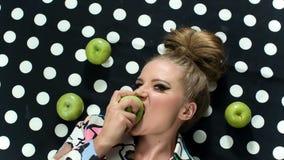 Het portret van de manierschoonheid van blonde mooi model die een appel bijten Speld op Stijl