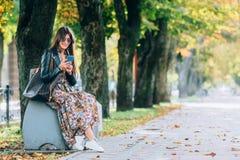 Het portret van de manierstad van modieuze hipstervrouw die mobiele telefoon, modieuze kleding, tennisschoenen, make-up, zonnebri stock foto