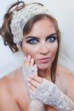 Het portret van de manierstudio van mooie jonge bruid met maakt op en in elegante handschoenen Royalty-vrije Stock Foto's