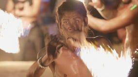 Het portret van de mens die de brand uitvoert toont op het strand bij nacht stock videobeelden
