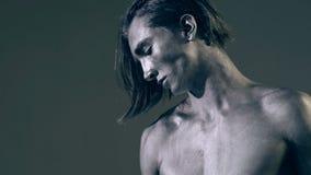 Het portret van de mens met zilveren lichaamskunst heft de domoor op grijze achtergrond op Knappe machts atletische mens in oplei stock video