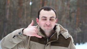 Het portret van de mens toont me gebaar in de winterbos roep stock videobeelden