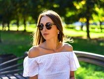 Het portret van de mooie donkerbruine zomer in zonnebril, witte blouse, park in, geniet van uw vakantie, de jeugdconcept Stock Afbeeldingen