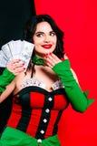 Het portret van de mooie glimlachende donkerbruine vrouw met maakt omhoog in rode en zwarte kleding met kaarten Royalty-vrije Stock Afbeeldingen