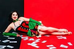 Het portret van de mooie glimlachende donkerbruine vrouw met maakt omhoog in rode en zwarte kleding met kaarten Stock Afbeelding