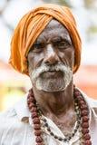 Het portret van de niet geïdentificeerde Sadhus-pelgrimsmens kleedde zich in oranje kleren, zittend op de weg, wachtend op voedse stock afbeeldingen
