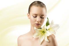 Het portret van de schoonheid met bloemen, kijkt zij lelies royalty-vrije stock foto's