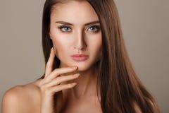 Het portret van de schoonheidsvrouw van tienermeisje het mooie vrolijke genieten van met lang bruin haar en schone huid die op wit stock afbeeldingen