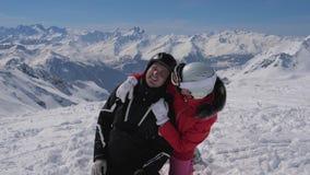 In het portret van de skitoevlucht van paarskiërs die het kussen koesteren en in de sneeuw vallen stock footage
