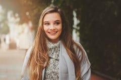 Het portret van de straatstijl van het jonge mooie gelukkige meisje lopen in de herfststad Royalty-vrije Stock Afbeeldingen