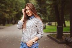 Het portret van de straatstijl van het jonge mooie gelukkige meisje lopen in de herfststad Stock Foto's