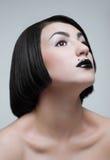 Het portret van de studio van jonge brunette met zwarte lippen Royalty-vrije Stock Afbeeldingen