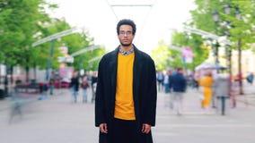 Het portret van de tijdtijdspanne van knappe Afrikaanse Amerikaanse student status in de straat stock videobeelden