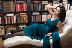Het portret van de voorraadfoto van de lezingsboek van de schoonheids jong vrouw in bibliotheek Royalty-vrije Stock Afbeelding