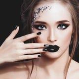 Het Portret van de Vrouw van de schoonheid De professionele Make-up en de Manicure met siverfolie schitteren, smokeyogen Zwarte k Stock Afbeeldingen