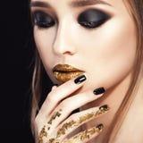 Het Portret van de Vrouw van de schoonheid Professionele Make-up en Manicure met gouden folie, smokeyogen Zwarte kleuren Royalty-vrije Stock Afbeelding