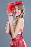 Het portret van de vrouwenmanier in rode uitstekende hoed met veren Stock Foto's