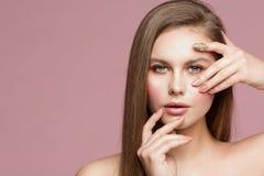 Het Portret van de vrouwenschoonheid, Modeltouching face die, Mooi Meisje Make-up en Spijkers tonen, die door Vingers kijken royalty-vrije stock foto
