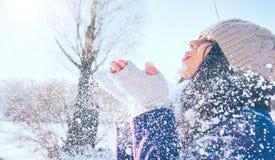 Het portret van het de wintermeisje Blazende sneeuw van het schoonheids de blije modelmeisje, die pret in de winterpark hebben Mo stock foto