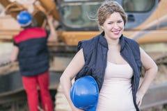 Het portret van de zwangere arbeidersvrouw met de mens die bulldozer in B herstellen stock afbeeldingen