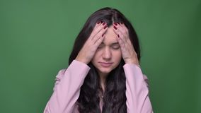 Het portret van donkerbruine onderneemster in roze jasje toont grote wanhoop en droefheid op groene achtergrond aan stock video