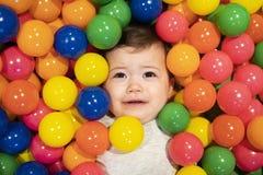 Het portret van een aanbiddelijke zuigeling op kleurrijke ballen heeft geen pret stock fotografie