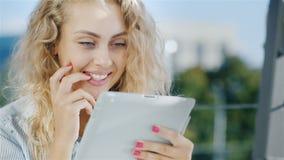Het portret van een aantrekkelijke jonge vrouw gebruikt tablet op een de zomergebied in de koffie Glimlachen, positieve emoties stock footage