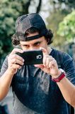 Het portret van een aantrekkelijke tienerjongen die zijn smartphone met zijn hand houden en neemt foto stock afbeelding