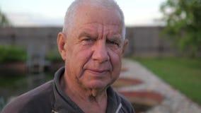 Het portret van een bejaarde, een grijs haar en diepe rimpels, bekijkt de camera stock videobeelden
