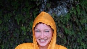 Het portret van een blauw-eyed vrouw in een gele regenlaag kijkt en glimlacht in de camera stock footage