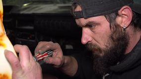 Het portret van een ernstige gebaarde werktuigkundige draait de schroeven met een schroevedraaier herstellend auto in garage stock videobeelden