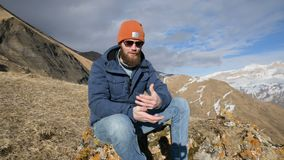 Het portret van een gebaarde reiziger in zonnebril en een GLB zit op een rots tegen de achtergrond van bergen het lachen en stock footage