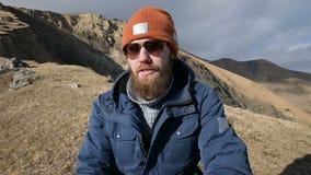Het portret van een gebaarde reiziger in zonnebril en een GLB zit op een rots tegen de achtergrond van bergen Het lachen stock video