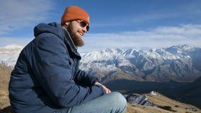 Het portret van een gebaarde reiziger in zonnebril en een GLB zit op een rots tegen de achtergrond van bergen Lacht en zegt stock video