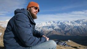 Het portret van een gebaarde reiziger in zonnebril en een GLB zit op een rots tegen de achtergrond van bergen zegt nr stock videobeelden