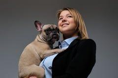 Het portret van een gelukkige kweker van de blondevrouw houdt haar leuke pug Geïsoleerdu op grijze achtergrond royalty-vrije stock foto