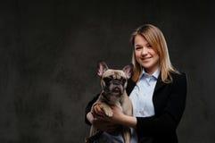 Het portret van een glimlachende kweker van de blondevrouw houdt haar leuke pug Geïsoleerd op donkere geweven achtergrond stock foto