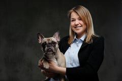 Het portret van een glimlachende kweker van de blondevrouw houdt haar leuke pug Geïsoleerd op donkere geweven achtergrond stock afbeeldingen
